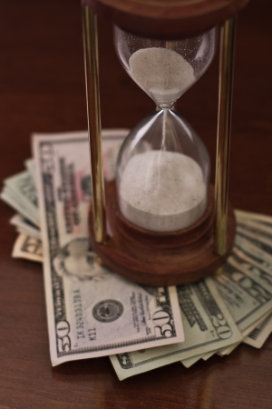 concept of an hour glass with time passing over money Stock Photo - 17445872