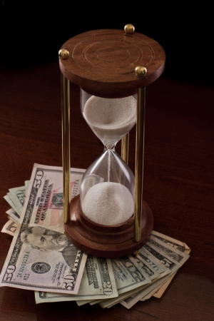 concept of an hour glass with time passing over money Stock Photo - 17445933