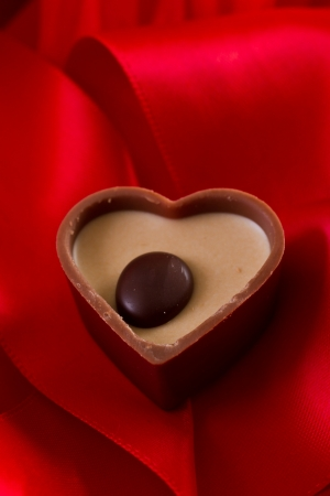 heart shaped milk chocolate with caramel cream on a red silk