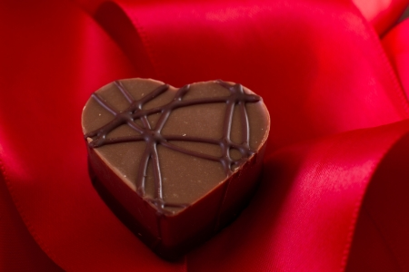 almond cream heart shaped chocolate on a red silk Stock Photo - 17445888