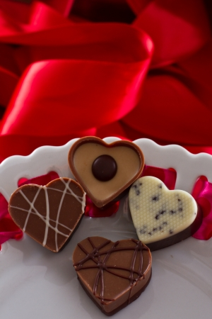 heart shaped chocolates on a white plate with red silk on the back Stock Photo - 17445894