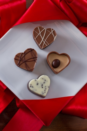 heart shaped chocolates on a white plate with red silk on the back Stock Photo - 17445927