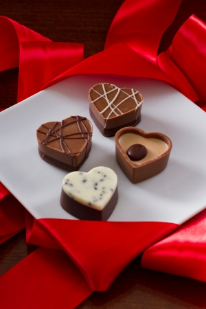 heart shaped chocolates on a white plate with red silk on the back Stock Photo - 17445907