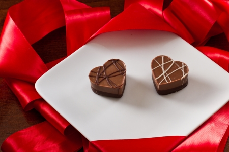 heart shaped chocolates on a white plate with red silk on the back Stock Photo - 17445893
