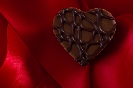 almond cream heart shaped chocolate on a red silk