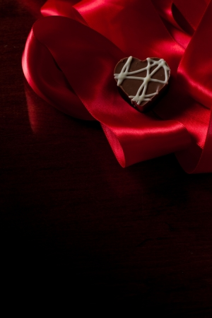 heart shaped chocolate hazelnut with cream and toffee on a red silk fading in to black Stock Photo - 17445903
