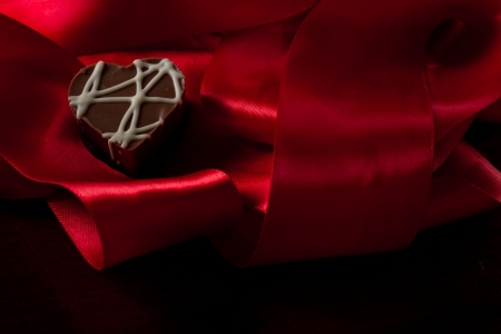 heart shaped chocolate hazelnut with cream and toffee on a red silk fading in to black Stock Photo - 17445871