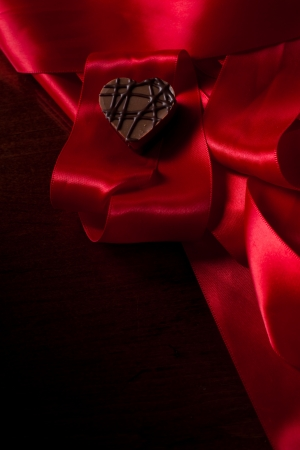 almond cream heart shaped chocolate on a red silk photo