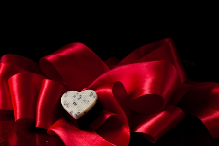 dark chocolate with cream and cocoa nibs on a red silk photo