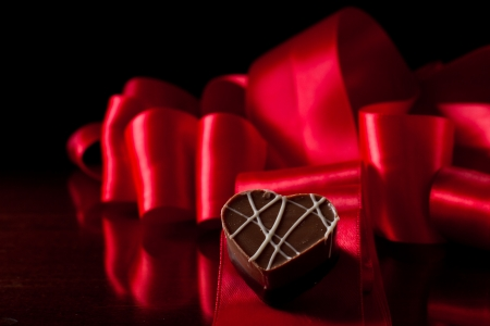 heart shaped chocolate hazelnut with cream and toffee on a red silk fading in to black Stock Photo - 17445876