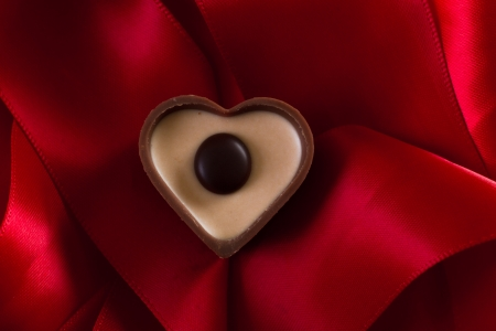 heart shaped milk chocolate with caramel cream on a red silk Stock Photo - 17439352