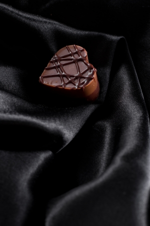 almond cream heart shaped chocolate on a dark silk photo
