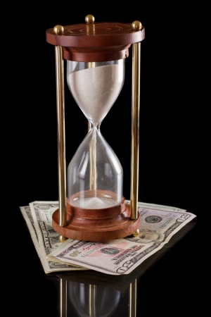 american dollars underneath a sand glass clock isolated on black Stock Photo