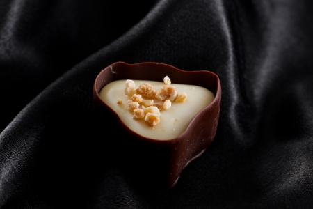 valentine s day: hand crafted chocolate dessert cups with praline filling on a dark silk background