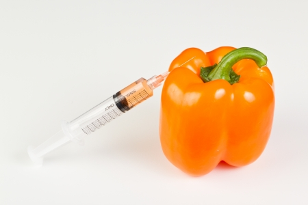 genetically modified organism: syringe with orange liquid next to a sweet pepper representing gmo, genetically modified organism or food Stock Photo