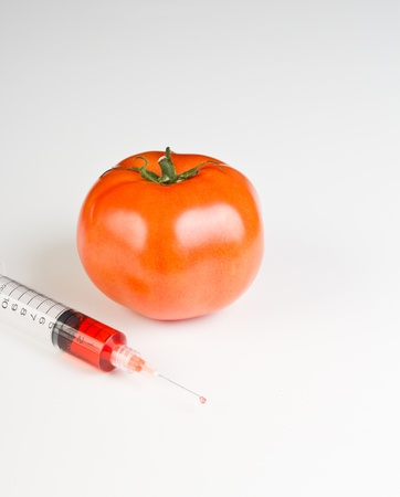 close up picture of a syringe with red liquid representing gmo juice and a tomato in the background on a white table