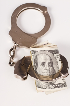 felony: silver handcuffs arresting hundred dollar bills on a white background