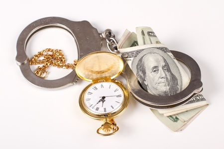 concept of doing jail time for money, handcuffs and time and money over a white background