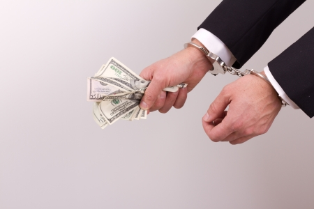 arrested businessman holding hundred dollar bills isolated on a white background Stock Photo - 17840650