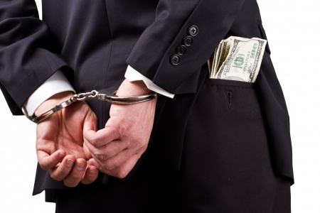 arrested businessman holding hundred dollar bills isolated on a white background Stock Photo - 17840678