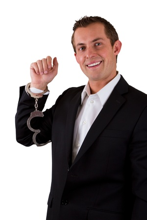 young business man smiling with handcuffs on isolated on a white background Stock Photo - 17799693