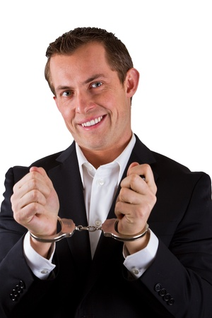young business man smiling with handcuffs on isolated on a white background photo