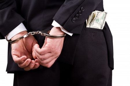 arrested businessman holding hundred dollar bills isolated on a white background Stock Photo - 17840679