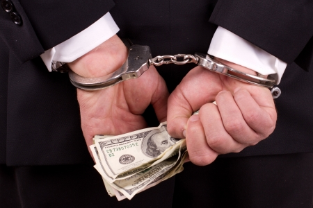 arrested businessman holding hundred dollar bills isolated on a white background Stock Photo - 17840680