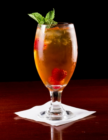 closeup of a challis with raspberry mint ice tea on a dark wood bar top fading into a black background photo