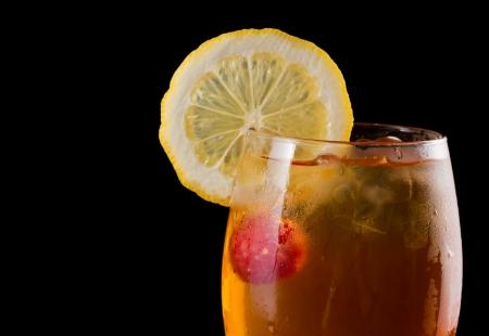 challis: raspberry iced tea garnished with a lemon wheel on a dark bar