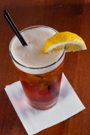 closeup of a long island red tea served on a dark bar top garnish with a lemon photo