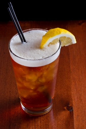 closeup of a long island red tea served on a dark bar top garnish with a lemon isolated on black Фото со стока