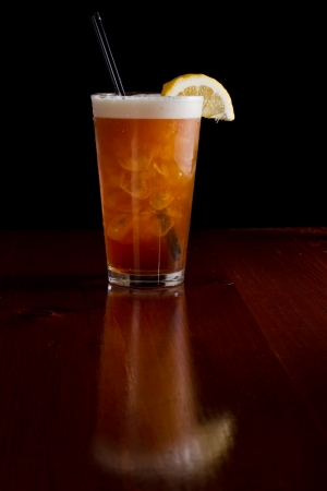 closeup of a long island red tea served on a dark bar top garnish with a lemon isolated on black photo