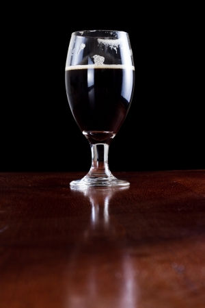 chalice with an irish dark beer isolated on a black background served on a bar photo