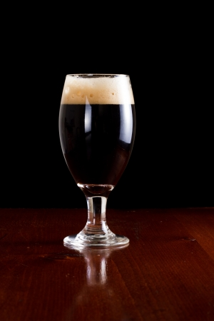 chalice with an irish stout beer isolated on a black background served on a bar photo
