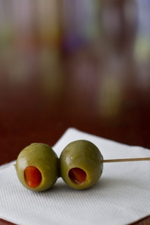 pimento: closeup of cocktail olives sitting on a white bar napkin with a shallow depth of field on a busy bar