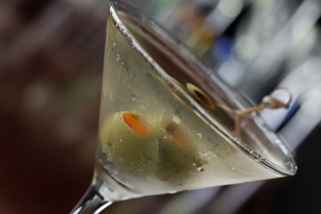 dirty martini chilled and served on a busy bar top with a shallow depth of field and color lights and glasses in the background photo