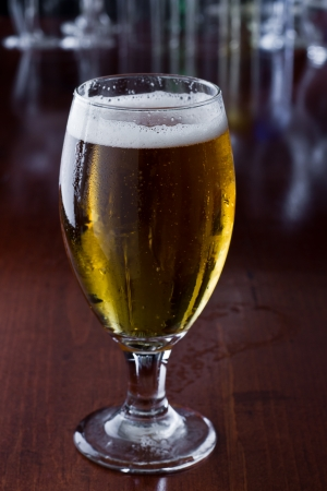 golden beer poured in to a chalice on a busy bar top with a shallow depth of field showing lights and glassware out of focus in the background photo