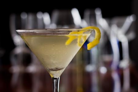 Dirty Martini gekoeld en geserveerd op een drukke bar top met een ondiepe scherptediepte en kleur verlichting en glazen op de achtergrond gegarneerd met een citroen twist Stockfoto