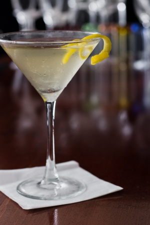 dirty martini chilled and served on a busy bar top with a shallow depth of field and color lights and glasses in the background garnished with a lemon twist