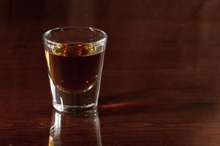 shot: shot glass on a dark bar top with splash of light reflecting Stock Photo