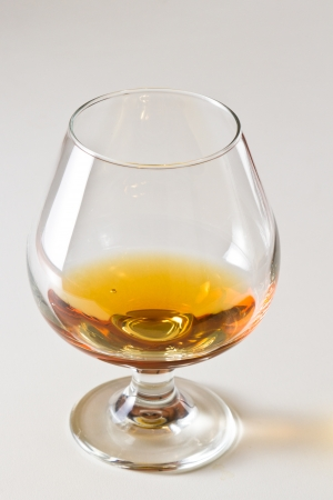closeup of a brandy snifter on a white table top with a golden reflection to the side photo