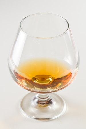 closeup of a brandy snifter on a white table top with a golden reflection to the side