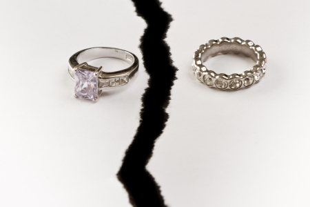 two rings on white ripped paper representing a broken relationship