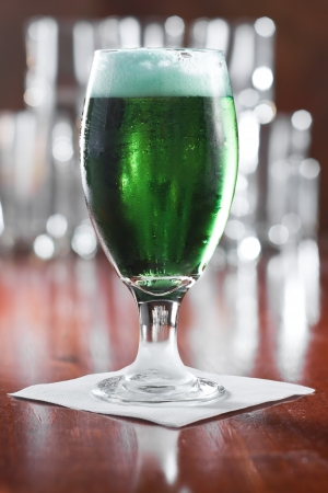 St. Patricks day green beer served in a chalice on a busy bar Stock Photo - 18281142