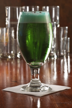 St. Patricks day green beer served in a chalice on a busy bar photo
