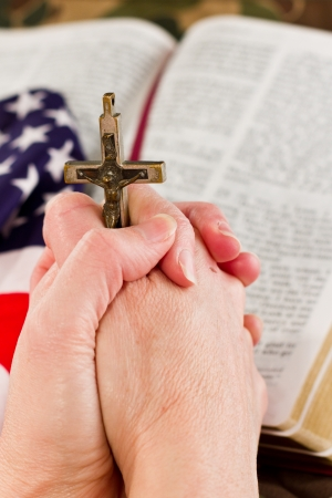 adult female hands holding a crucifix with a camouflage background and an open bible with an American flag to the side photo