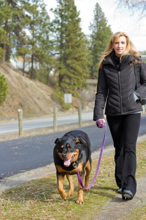 attractive young woman walking her Rottweiler in the park photo