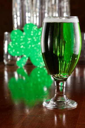 Saint Patricks day beer srved on a bar top with a green shamrock photo