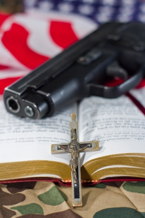 crucifix with an open bible, a gun and an american flag in the background with a shallow depth of field photo